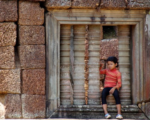From the look on this girl's face, to the size and scale of the 'window' that's been built into the temple wall, everything in this photo is what Angkor Wat.